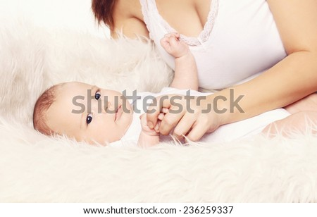 Cute baby and mother lying on the bed at home - stock photo