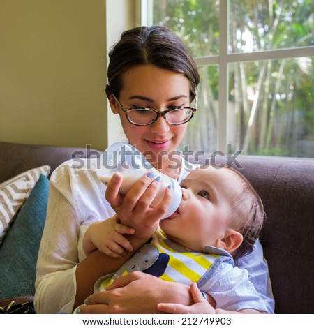 Cute baby boy being fed milk by a pretty young woman in a home setting. - stock photo