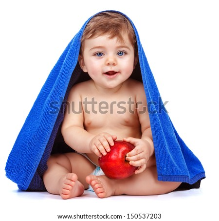 Cute baby boy covered with blue towel holding in hands red fresh apple, sweet child after bath, healthy lifestyle, kids nutrition, happy childhood concept  - stock photo