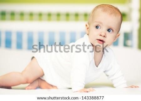 Cute baby boy crawling at home. - stock photo