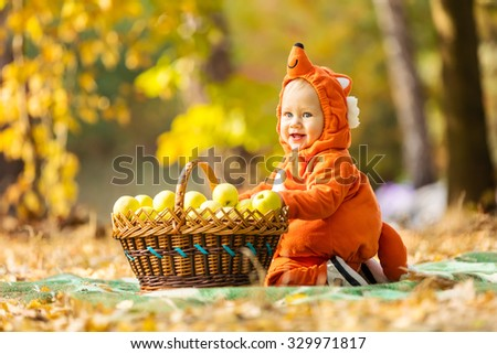Cute baby boy dressed in fox costume sitting by basket with apples in autumn park - stock photo