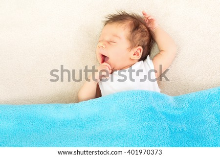 Cute baby boy in bed, covered with blue soft fleece blanket, yawning and sleeping. High angle view, copy space, mild retouch. - stock photo