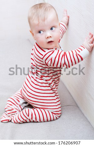 Cute baby boy learning to crawl and stand up - stock photo