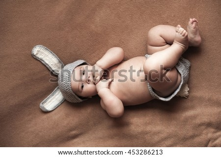 Cute baby boy lie naked on a beige background wearing a crochet hat in the form of a Christmas bunny with ears and tail - stock photo