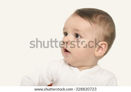 Cute baby boy looking to the side surprised. Adorable baby portrait looking curious isolated on white. - stock photo