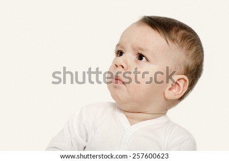 Cute baby boy looking up upset. Baby looking sad. Isolated on white. - stock photo