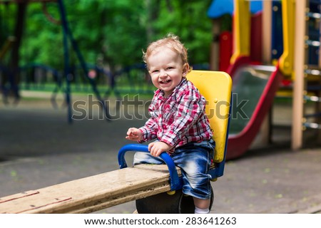 Cute baby boy on a seesaw swing at the playground - stock photo