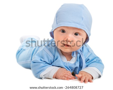 Cute baby boy on his tummy on a white blanket, in blue clothes with a hat on his head, looking at the camera with a curious and inquisitive expression - stock photo