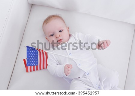 Cute baby boy on white couch with American flag, view from above - stock photo