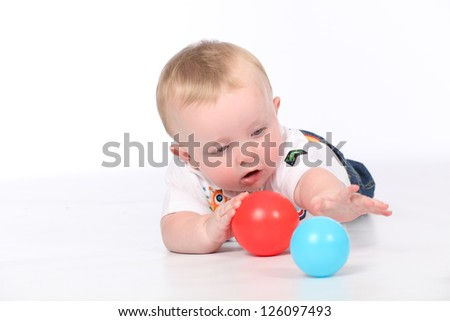 Cute baby boy playing in isolated white studio, with colorful balloons for his birthday - stock photo