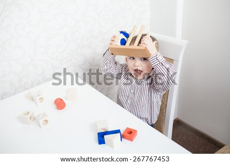 Cute baby boy playing with blocks on the table - stock photo