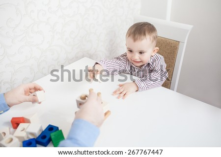 Cute baby boy playing with blocks with father - stock photo