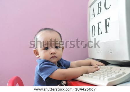 Cute baby boy playing with computer, part of early education process. - stock photo