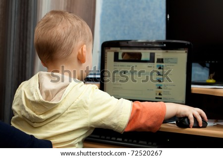 Cute baby boy playing with laptop - stock photo