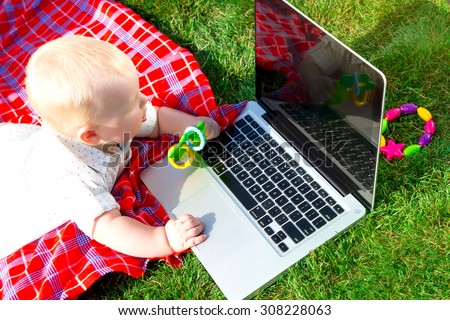 Cute baby boy playing with laptop and toys outdoors on green grass.Wondered baby looks at notebook screen.little boy playing outdoors with a laptop.baby boys face getting into on a laptop computer     - stock photo