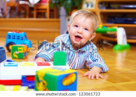 cute baby boy playing with toys in living room - stock photo