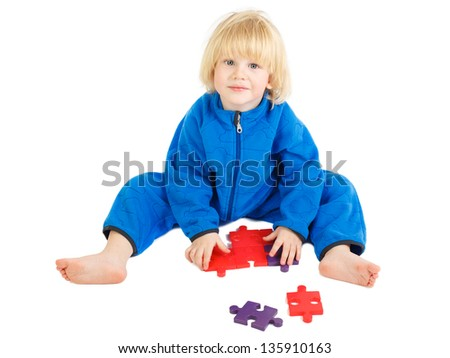 Cute baby boy sits on a floor and plays with construction set - stock photo