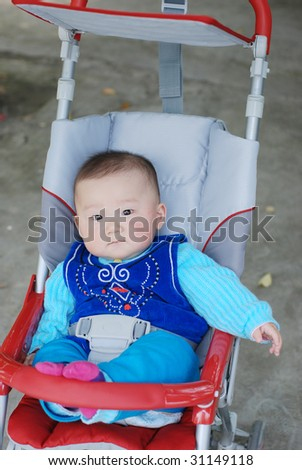 cute baby boy sitting in red baby carriage - stock photo