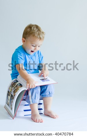 cute, baby boy sitting on a pile of books and reading - stock photo