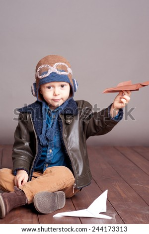 Cute baby boy wearing stylish leather jacket and aviator cap over gray. Playing with paper origami planes in room. Sitting on wooden floor. Looking at camera. Childhood. - stock photo