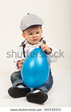 Cute baby boy with eyeglasses and hat playing with blue balloon - stock photo