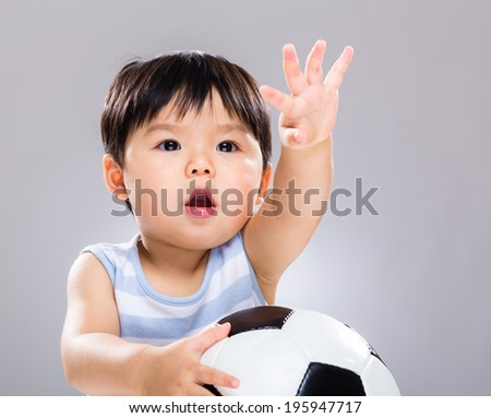 Cute baby boy with football - stock photo