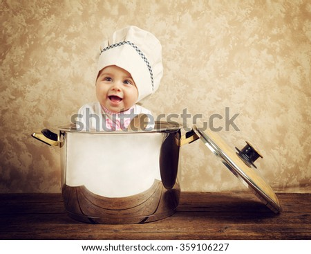Cute baby chef in a huge cauldron on wooden table - stock photo