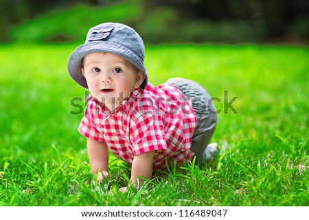 Cute baby crawling in the grass - stock photo