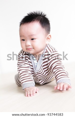 Cute Baby crawling on living room floor with home background, baby is a cute asian child - stock photo