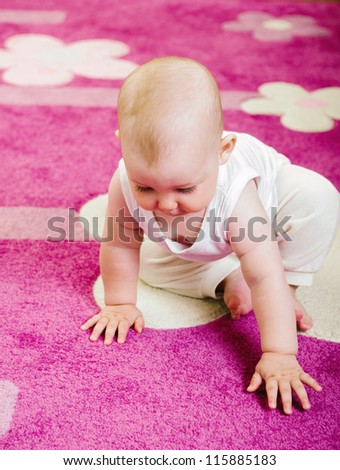 Cute baby crawling on soft pink carpet - stock photo