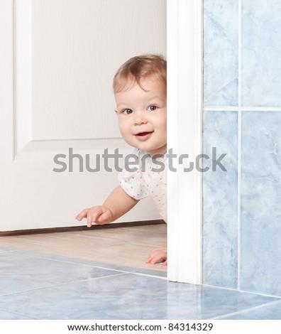 cute baby crawling through the white door - stock photo