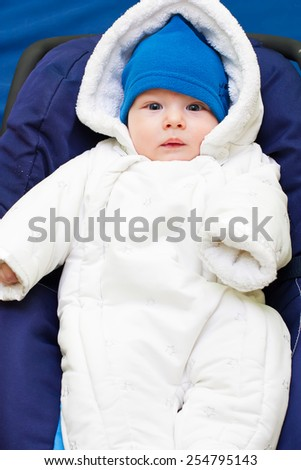 Cute baby dressed in warm fluffy winter clothes. - stock photo