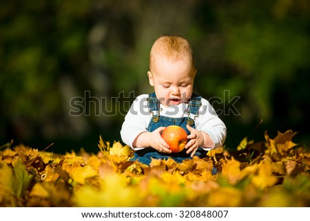 Cute baby eating apple outdoor in fall sunny day - sitting in leaves - stock photo