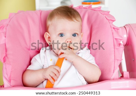Cute baby eating carrot - stock photo