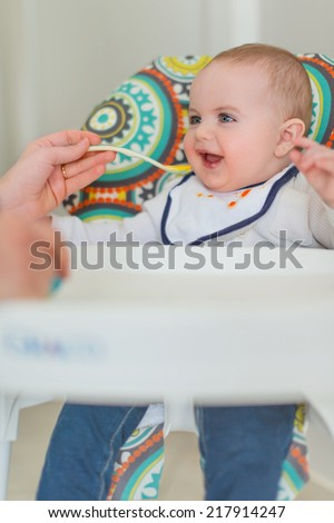 Cute baby eating puree - stock photo