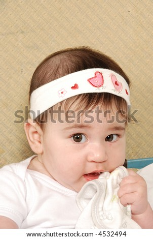 cute baby girl chewing on bib - stock photo
