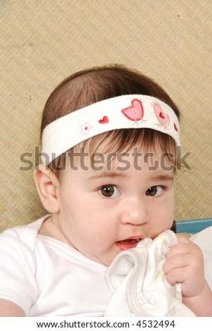 cute baby girl chewing on bib - stock photo