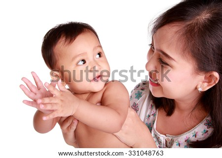 Cute baby girl clapping hands and looking back at her mom, isolated on white background - stock photo