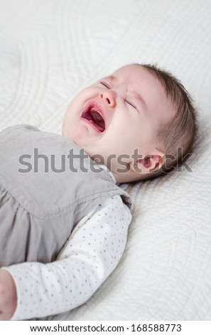 Cute baby girl crying over white bedcover - stock photo