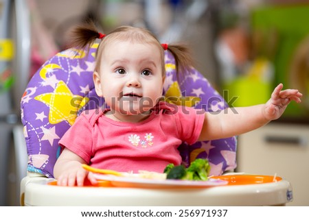 cute baby girl eating healthy food on kitchen - stock photo