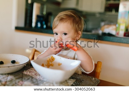 Cute baby girl eating milk with cereals for her breakfast in the kitchen - stock photo