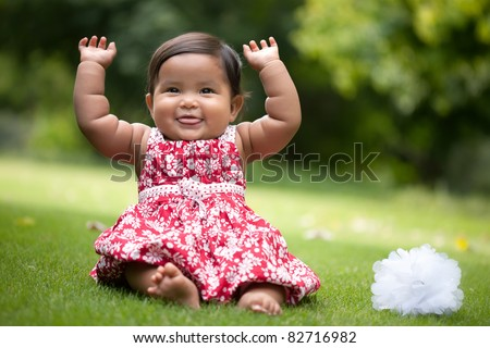 cute baby girl gesturing with her arms up and blowing raspberries - stock photo