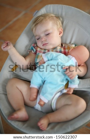 Cute baby girl having sweet dreams sleeping quiet in a bouncer holding doll in her arm - stock photo