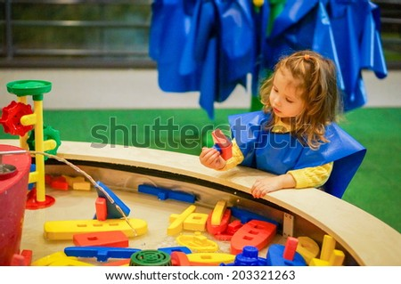 Cute baby girl is playing with water in museum - stock photo