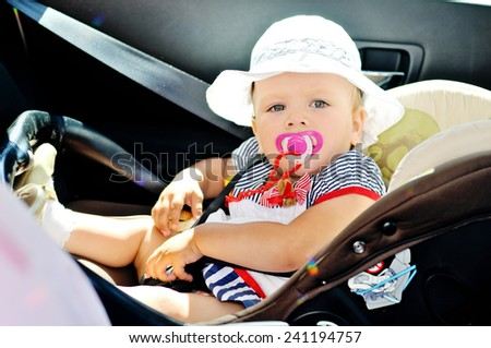 cute baby girl is sitting in car seat - stock photo