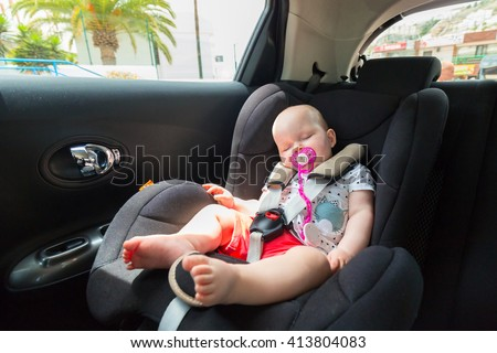 Cute baby girl is sleeping in the car on child safety seat - stock photo