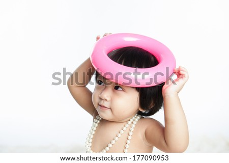 Cute baby girl looking to the side excited, wearing necklace isolated white background - stock photo