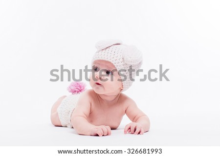 Cute baby girl lying naked on a white background wearing a hat in the form of a Christmas bunny with pink ears and tail, with depth of field Photo - stock photo