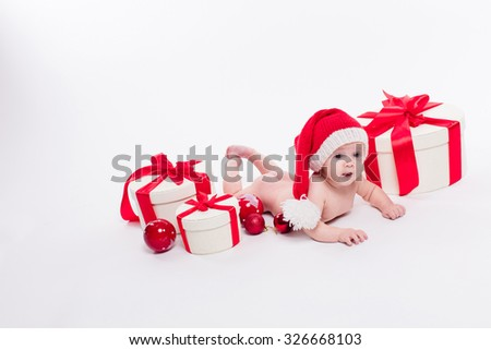 Cute baby girl lying naked on her stomach on a white background in a red New Year's cap among red Christmas balls and red boxes with gifts picture with depth of field - stock photo