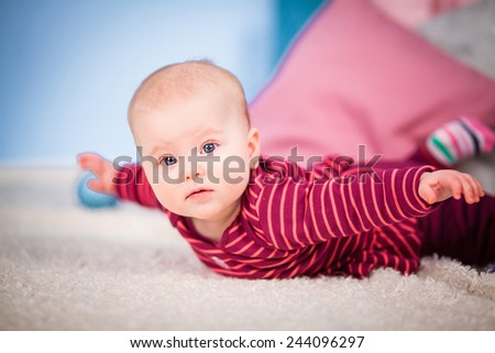 Cute baby girl lying on the carpet beside the pillows - stock photo